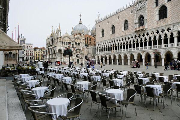 Пустые столики перед рестораном на площади Сан - Марко в Венеции