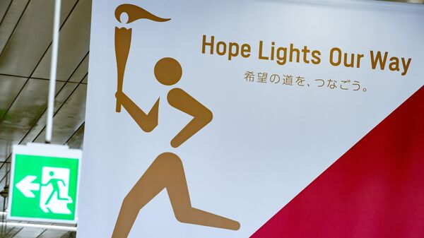 A poster for the Tokyo 2020 torch relay (R) is pictured inside Fukushima railway station in Fukushima Prefecture on March 24, 2020. - The Olympic torch relay, due to begin on March 25 from a symbolic site in Fukushima, will proceed as scheduled but organisers said they would re-assess in the coming days given the worsening COVID-19 coronavirus situation. (Photo by Philip FONG / AFP)