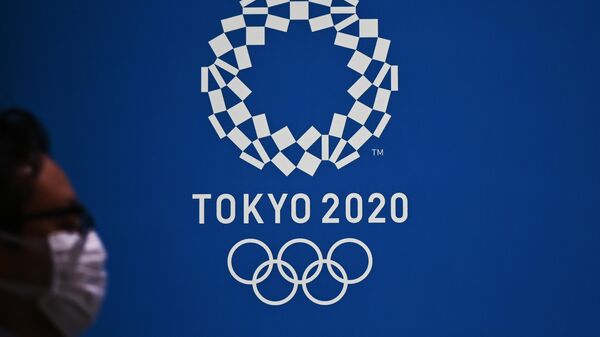 Мужчина проходит мимо логотипа Олимпийских игр-2020 в Токио