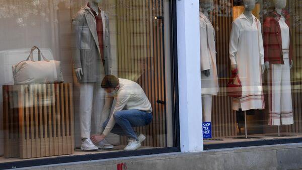 Сотрудник магазина оформляет витрину
