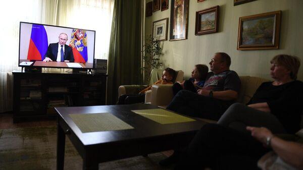 Жители Москвы смотрят у себя дома трансляцию обращения президента России Владимира Путина к гражданам из-за ситуации с коронавирусом