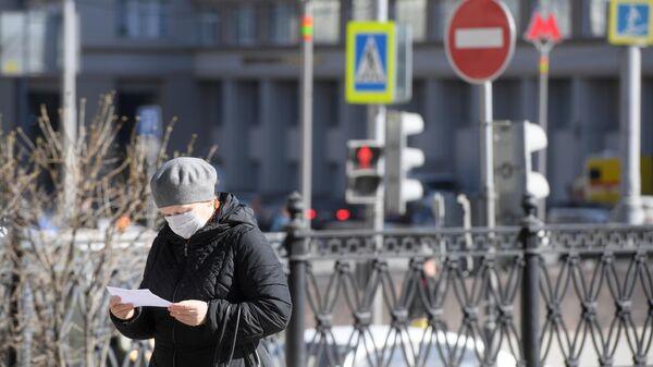 Женщина в защитной маске на одной из улиц в Москве