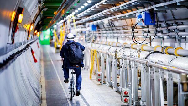 Мужчина едет на велосипеде вдоль Большого Адронного Коллайдера в туннеле Европейской организации ядерных исследований (ЦЕРН)