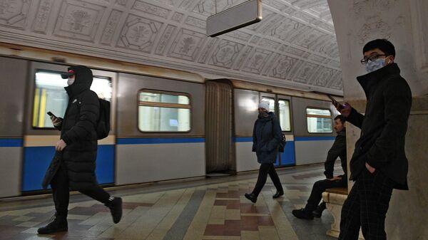 Пассажиры в медицинских масках на одной из станций метро в Москве