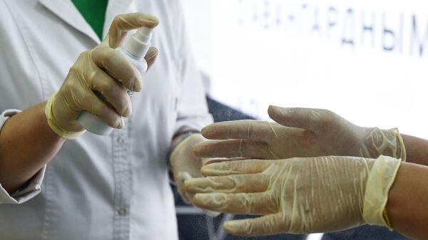 Медработники дезинфицируют свои руки в аэропорту Толмачево в Новосибирске