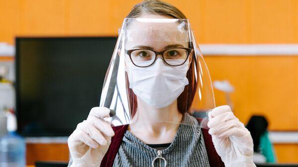 Девушка демонстрирует готовый лицевой экран для индивидуальной защиты глаз, дыхательных путей и лица медицинских работников в технопарке Кванториум. Новатория