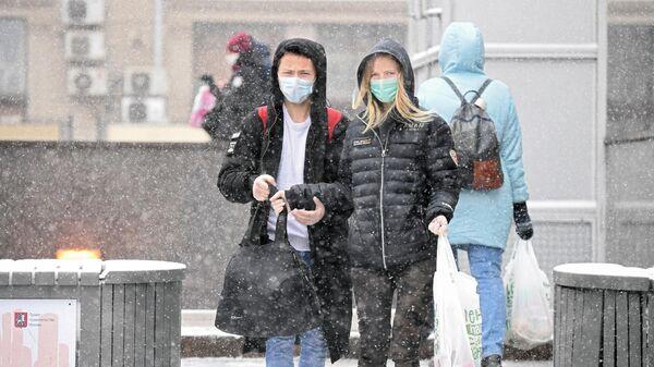 Молодые люди в медицинских масках на одной из улиц в Москве