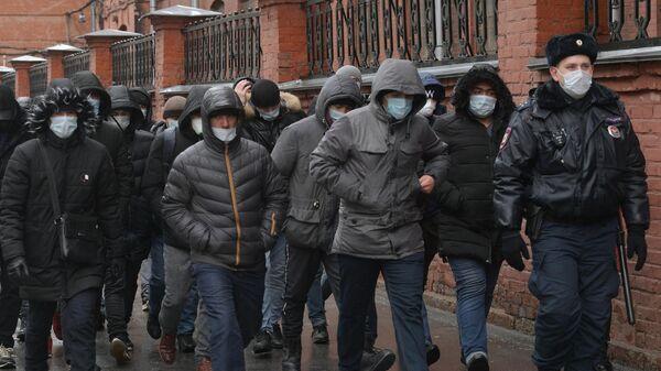 Сотрудник полиции выстраивает в очередь мигрантов у здания УФМС в Санкт-Петербурге