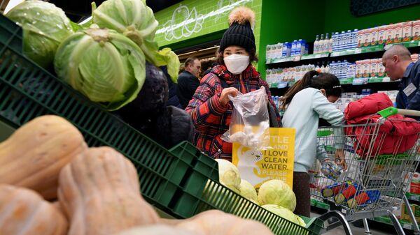 Покупательница выбирает чеснок в одном из супермаркетов в Москве