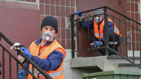 Сотрудники коммунальной службы проводят санитарную обработку парадной в Санкт-Петербурге