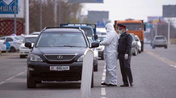 Медик измеряет температуру водителям на въезде в Бишкек