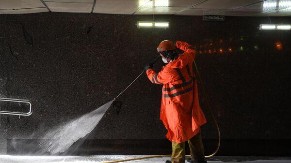 Сотрудник коммунальных служб во время уборки в одном из подземных переходов Москвы