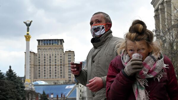 Бездомные люди во время раздачи бесплатных обедов на Площади Независимости в Киеве