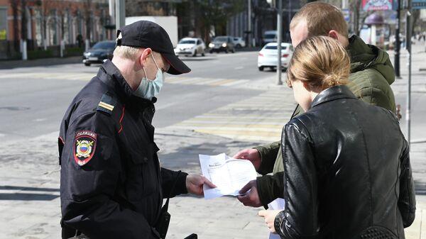 Сотрудник полиции проверяет документы у прохожих во время патрулирования улиц в Ростове-на-Дону