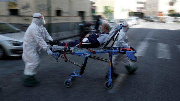 Медики в защитных костюмах перевозят пациента по улице в Неаполе