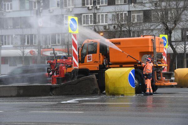 Сотрудник коммунальных служб во время уборки на улице Новинский бульвар в Москве.