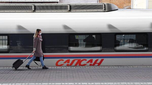 Пассажир у поезда Сапсан на Ленинградском вокзале в Москве