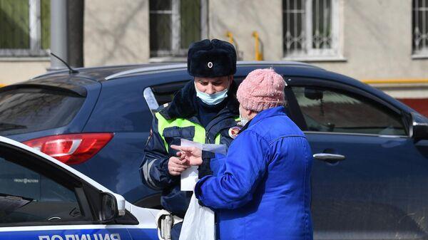 Сотрудник полиции общается с жительницей Москвы в дни режима самоизоляции граждан в связи с распространением коронавируса
