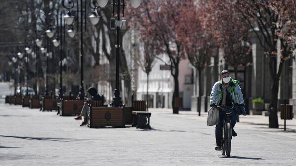 Велосипедист в защитной маске на улице Пушкина в Симферополе