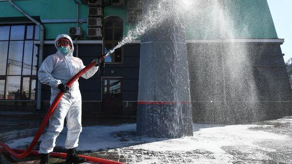 Сотрудник МЧС во время дезинфекции территории железнодорожного вокзала Новосибирск-Главный