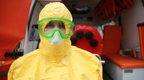 Врач бригады скорой помощи в защитном костюме