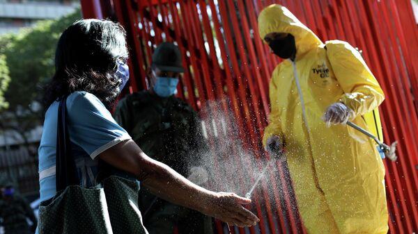 Дезинфекция рук при входе на рынок во время пандемии коронавируса в Каракасе