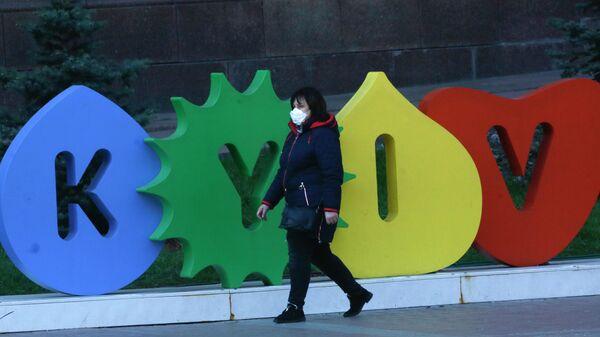 Женщина в защитной маске на одной из улиц в Киеве, Украина