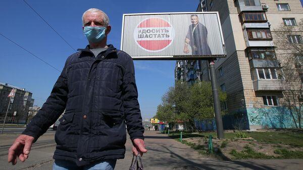 Мужчика в защитной маске у рекламного щита, установленного в Киеве в связи с коронавирусом