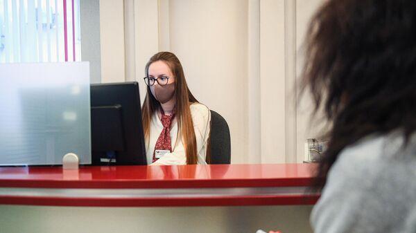 Сотрудница банка в защитной маске ведет прием посетителей в одном из отделений Московского кредитного банка
