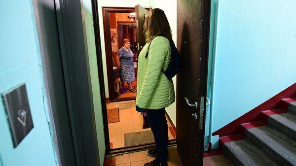 Социальный работник передает доставленные на дом продукты пенсионерке в Москве