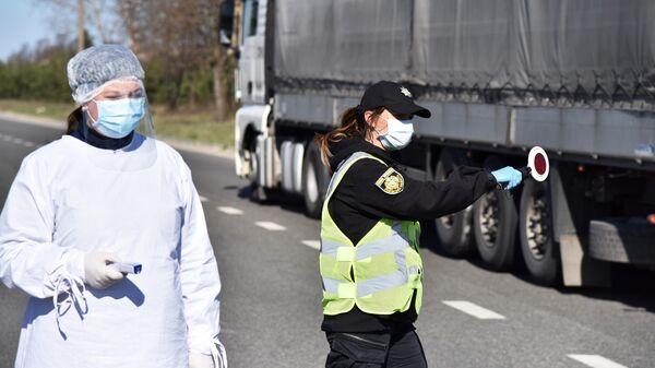 Медицинский работник и сотрудник правоохранительных органов Украины проверяют водителей на блокпосте во Львовской области