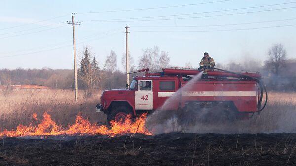 Сотрудник пожарной службы тушит полевой пожар