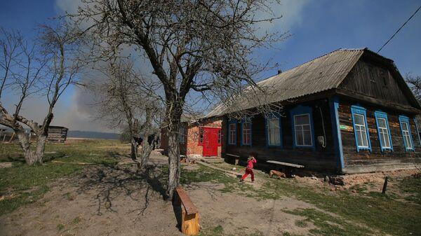 Дым от пожара в Чернобыльской зоне отчуждения над частным домом в селе Раговка