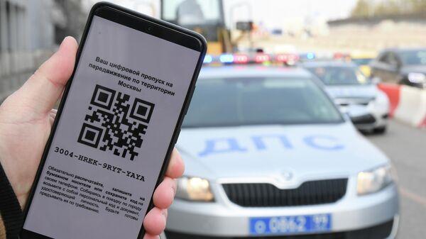 Житель Москвы демонстрирует цифровой пропуск для передвижения по городу