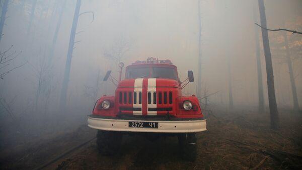 Пожарный автомобиль во время тушения огня, возникшего в районе села Полесское и дошедшего до границы села Раговка, на территории зоны отчуждения Чернобыльской АЭС на Украине, где уже почти неделю не прекращаются лесные пожары