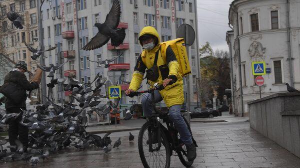 Сотрудник службы доставки Яндекс. Еда на велосипеде у метро Арбатская в Москве