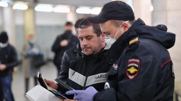Пассажир метро показывает код своего электронного пропуска на экране смартфона сотруднику полиции на станции метро Сокольники в Москве