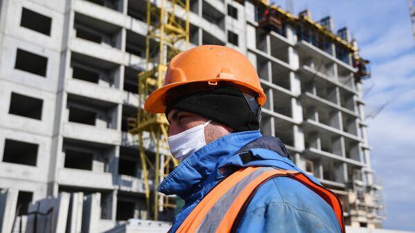 Рабочий в медицинской маске на строительстве жилого комплекса