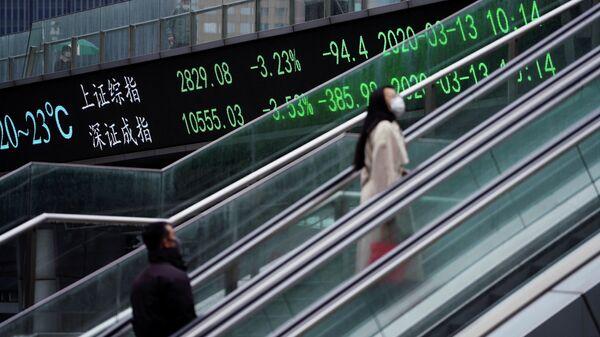 Люди в защитных масках проезжают на эскалаторе мимо табло с индексами Шанхайской и Шэньчжэньской фондовых бирж