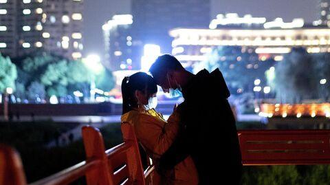 Пара в защитных масках на берегу реки Янцзы в Ухане, провинция Хубэй
