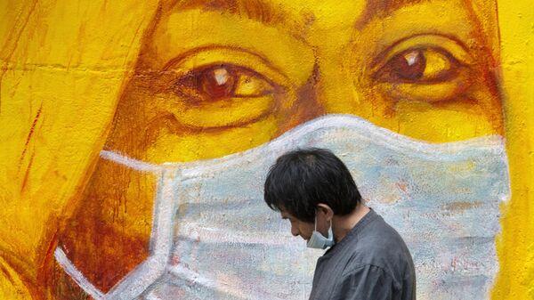 Прохожий около стены с изображением человека в маске в Гонконге