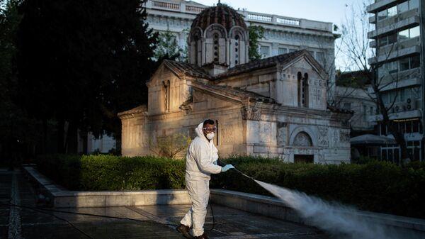 Муниципальный работник  дезинфицирует площадь вокруг собора в Афинах