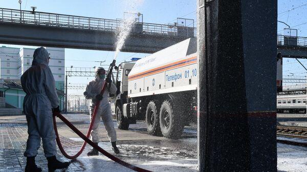 Сотрудники МЧС во время дезинфекции территории железнодорожного вокзала Новосибирск-Главный