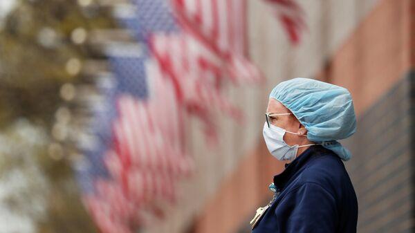 Медсестра в защитном снаряжении у больницы Элмхерст в районе Квинс в Нью-Йорке