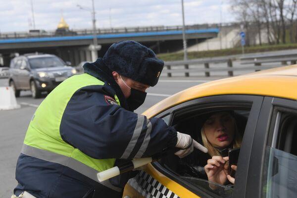 Инспектор дорожно-патрульной службы проверяет у пассажира такси цифровой пропуск на передвижение по Москве