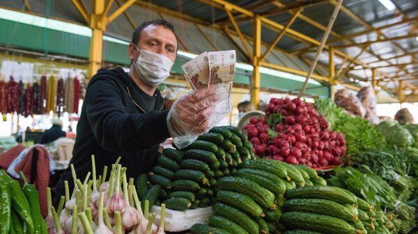 Продавец овощей в медицинской маске на Центральном рынке Адлерского района Сочи