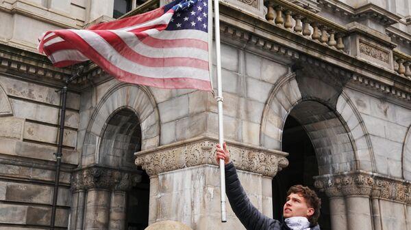 Участник акции с требованием отмены карантина в США на одной из улиц Олбани