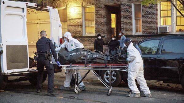 Сотрудник полицейского управления Нью-Йорка помогает рабочим вынести тело из дома в  Бруклине, Нью-Йорк