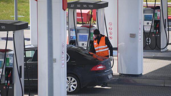 Заправщик заправляет автомобиль на одной из автозаправочных станций в Москве