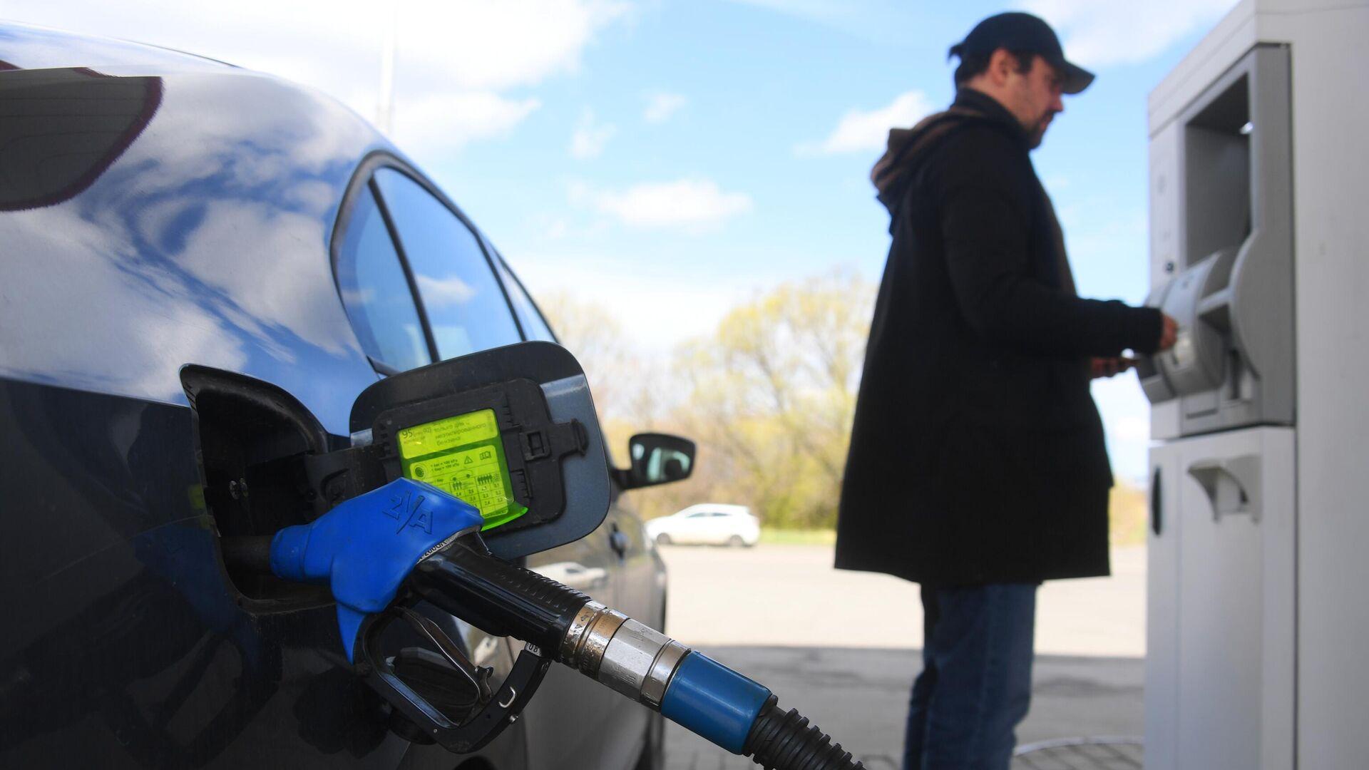 Мужчина оплачивает автомобильное топливо на одной из АЗС в Москве - РИА Новости, 1920, 12.11.2020